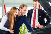 Seller or car salesman and clients or customers in car dealership presenting the engine performance of new and used cars in the showroom, the men looking under the hood