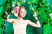 stock photo of loach  - Beautiful young woman standing under an arch of flowers and overgrown loach - JPG
