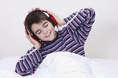 stock photo of preteen  - preteen boy listening music in the room - JPG