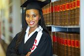 stock photo of laws-of-attraction  - beautiful african female graduate in library on graduation day - JPG