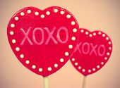 picture of some heart-shaped lollipops with the text XOXO, hugs and kisses, written in them, with a