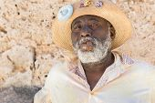 HAVANA,CUBA - JANUARY 20, 2014:Afrocuban man smoking a cigar near the Cathedral Square.Characters li