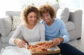 Cheerful couple at home having pizza for supper