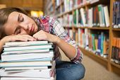 Dozing student sitting on library floor leaning on pile of books in college