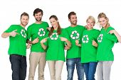 Group portrait of young people in recycling symbol t-shirts pointing to themselves over white backgr