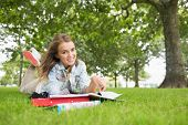 Happy young student lying on the grass studying on college campus