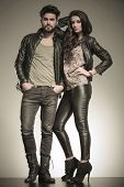 in love couple dressed in leather clothes in a fashion pose in studio