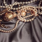 art vintage golden and pearl bijouterie with scarab on  gray silk background in peach sepia; square