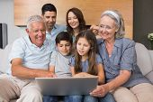 Happy extended family using laptop on sofa in the living room at home