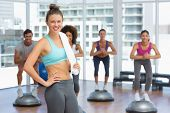 picture of step aerobics  - Portrait of a smiling woman with fit people performing step aerobics exercise in gymPortrait of a smiling woman with fit people performing step aerobics exercise in gym - JPG