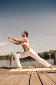 image of tai-chi  - young woman making tai chi exercise at a lake - JPG
