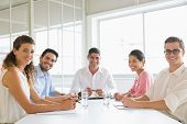 Portrait of confident business people sitting at conference table in office