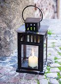 Lamp With Burning Candle Standing On The Stone Pavement