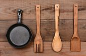 Closeup of a cast iron frying pan and wooden utensils hanging on the wall of a rustic kitchen.
