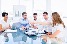 picture of half-dressed  - Smartly dressed executives shaking hands during a business meeting in the office - JPG