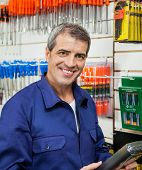 Portrait of confident worker holding packed product in hardware store