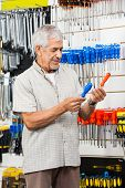 Senior male customer comparing screwdrivers in hardware shop