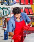 Young salesman with drill bit and toolbox in hardware store