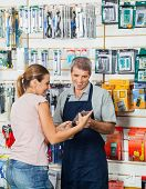 Mature salesman guiding female customer in hardware store