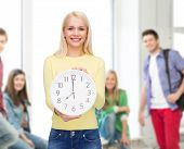 time, education and people concept - smiling young woman with wall clock showing 8