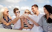vacation, travel, sea, friendship and people concept - smiling friends with glasses of champagne on