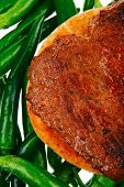 meaty food : roast meat steak on arabic pita bread over green hot chili peppers on a white background