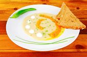 homemade cuisine : salmon soup served with bread and pepper on white dish on wooden table