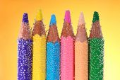 Colorful pencils in water with bubbles on yellow background