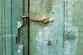stock photo of hook  - The green vintage door is closed on rusty iron retro hook