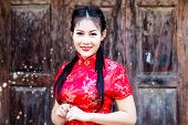 pic of traditional attire  - Chinese girl in traditional Chinese cheongsam blessing - JPG