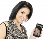 Closeup of a happy teen girl showing her phone to the viewer with her self-ie image.  On a white bac