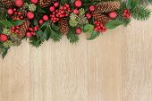 Christmas background border with decoration of red baubles, holly, winter greenery and pine cones ov