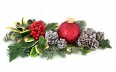 Christmas decoration with holly, red baubles, mistletoe, ivy, fir and cedar leaf sprigs with snow co