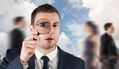 Businessman looking through magnifying glass against blue sky with white clouds