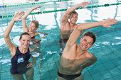 Happy fitness class doing aqua aerobics in swimming pool at the leisure centre