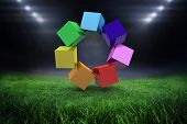 3d colourful cubes in a circle against football pitch with bright lights