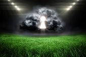 Keyhole in grey cloud against football pitch with bright lights