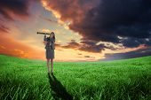 Businesswoman looking through a telescope against green field under orange sky