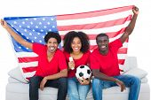 Happy football fans in red sitting on couch with usa flag on white background