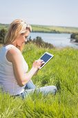 Pretty blonde sitting on grass using her tablet on a sunny day in the countryside