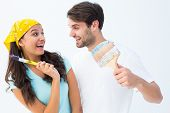 Happy young couple painting together and laughing on white background