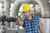 Confident young male worker pointing away in industry