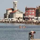 Piran, Slovenia - 15 June 2009: People on pier and in the sea on a coast in Piran, Slovenia.
