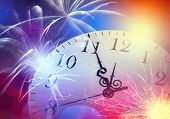 Conceptual image of clock with bokeh lights and firework
