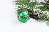 Green And Gold Christmas Ornament With Fir Branch In Background