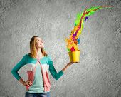 Young girl holding bucket with colorful splashes