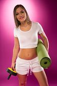 Fit woman carrying exercise equipment standing on fuchsia background