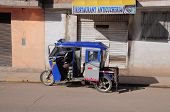 A trishaw with driver and passenger.