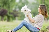 pic of maltese  - Young woman with a maltese dog in the park - JPG