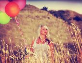 a pretty woman enjoying summer outside with a bunch of balloons toned with a retro vintage instagra